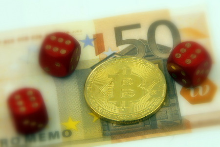 Golden physical Bitcoin cryptocurrency and 3 pairs with 6 dice symbolizing the concept of cryptocurrency by 50 Euro banknote (selective focus). Stock Photo