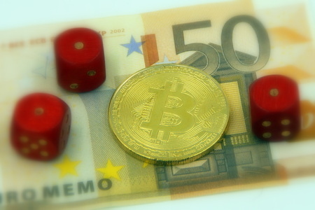 Golden physical bitcoin cryptocurrency and 3 pairs with 1 dice symbolizing the concept of cryptocurrency by 50 Euro banknote (selective focus).