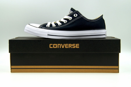 Black Chuck Taylor Converse All-Star standing on a retail box, against a white background.