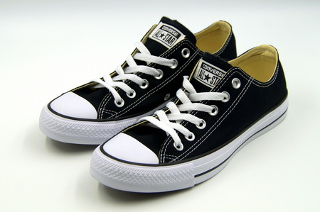Black Chuck Taylor Converse All Star low tops against a white background.
