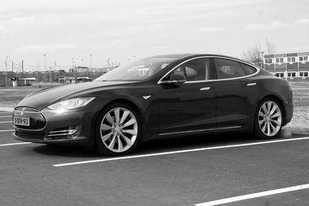 Electric Tesla Motors Model S parked on a parking lot (black white). Tesla Motors is an American automotive and energy storage company.