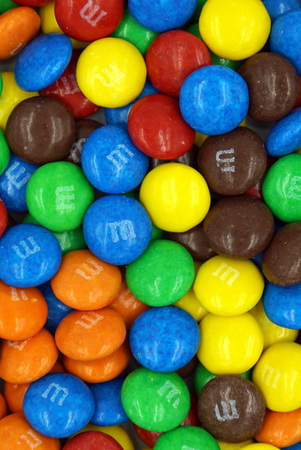 Pile or button-shaped M & M chocolates background. M & M's is a product of the Mars Wrigley Confectionery division of Mars, Incorporated.