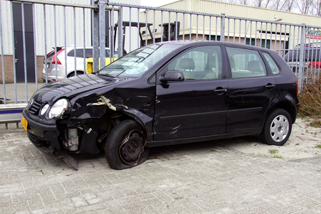 Volkswagen Polo with damage parked by the side of the road.