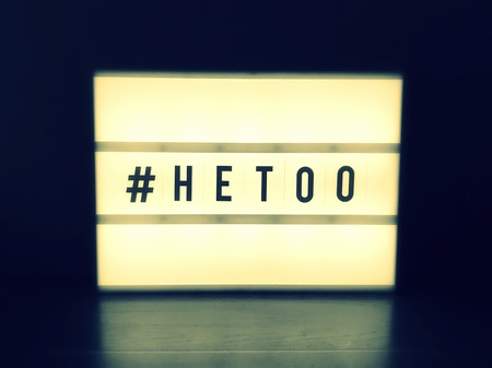 #Hetoo hashtag word on glowing lightbox. Anti sexism protest movement against inappropriate behavior towards man (selective focus)