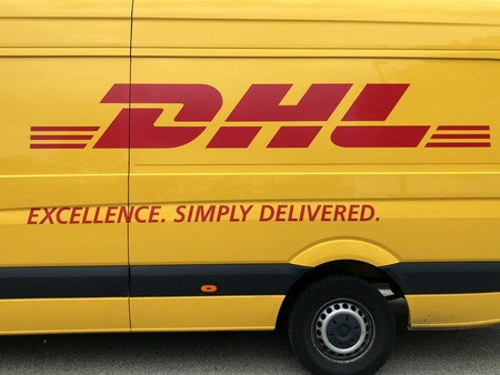 Lelystad, the Netherlands - August 21, 2018: Side view at the logo of a yellow DHL from.