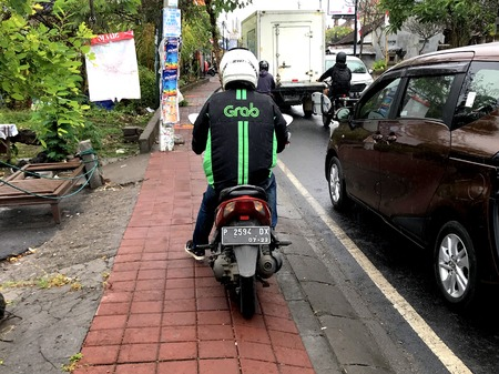 Bali, Indonesia - August 17, 2018: Backside of a unidentifiable Grab motorbike taxi driver standing boy the side of the road. Grab is a motor taxi transportation service. 에디토리얼