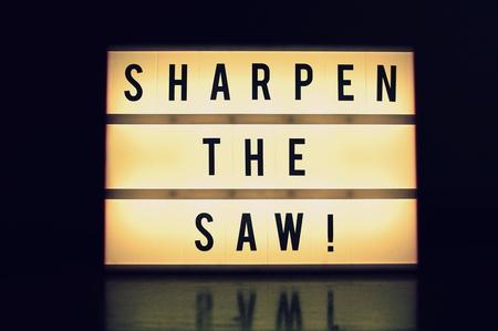 'Sharpen the saw' text glowing on a lightbox Stok Fotoğraf