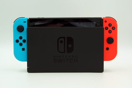 Amsterdam, The Netherlands - November 20, 2018: Docked Nintendo Switch against a white background.