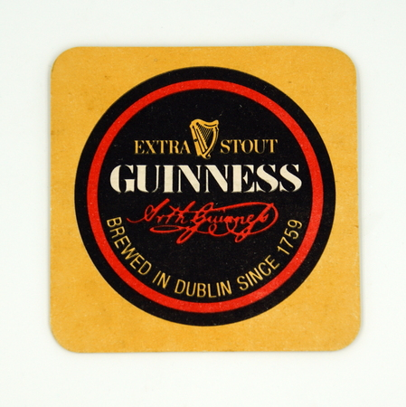 Amsterdam, the Netherlands - March 12, 2019: 1980s vintage Guinness Foreign Extra Stout beer mat or coaster against a white background.
