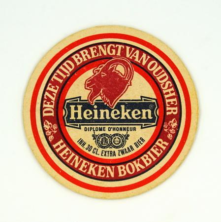 Amsterdam, the Netherlands - March 15, 2019: 1980s vintage Heineken beer mat or coaster against a white background.