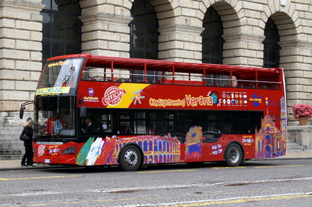 Verona, Italy - April 29, 2019: Unknown and unidentifiable participants entering a Red Geryery panorama double decker sightseeing bus in the city of Verona.