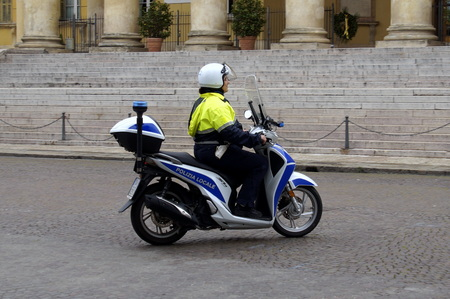Verona, Italy - April 29, 2019: Unknown and unidentifiable Italian local police officer driving a scooter in the city center of Verona.