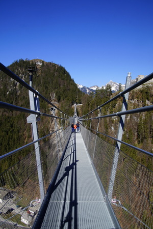 Reutte, Tyrol, Austria - April 20, 2019: Unknown and unidentifiable participants walking on the suspension footbridge Highline179.