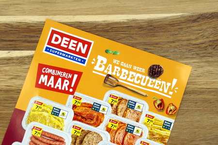 Amsterdam, the Netherlands - May 12, 2019: Grocery shop sale flyer or Dutch supermarket Deen advertising meat products, against a wooden background. Редакционное