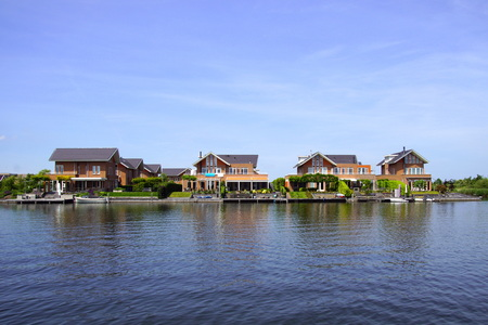 Noorderplassen, Almere, The Netherlands - June 1, 2019: Dutch houses on the waterside in the city of Almere.