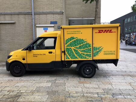 Almere, the Netherlands - July 6, 2019: Yellow electrical DHL delivery from parked by the side of the road. Nobody in the vehicle.