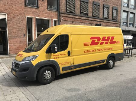 Roskilde, Denmark - July 19, 2019: Yellow DHL delivery from parked by the side of the road. Nobody in the vehicle.
