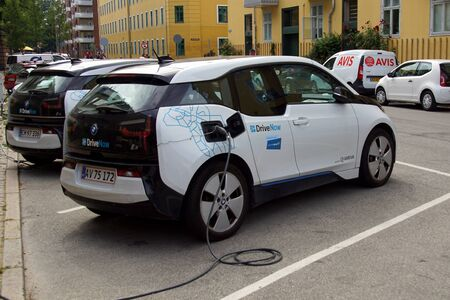 Copenhagen, Denmark - July 20, 2019: DriveNow BMW i3 electric car being charged on a public parking lot. Nobody in the vehicle.