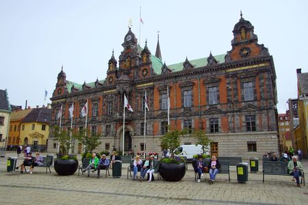 Malmo, Sweden - July 22, 2019: Unknown participants sitting in front of the town hall of Malmo at Stortorget square.