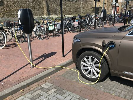 Lelystad, the Netherlands - August 25, 2019: Matt brown Volvo CX90 being charged on a parking lot.
