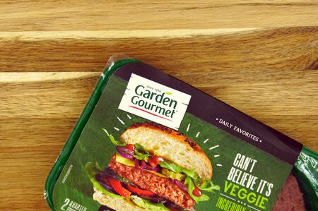 Amsterdam, the Netherlands - August 20, 2019: Green package or Garden Gourmet Incredible Burger against a wooden background.