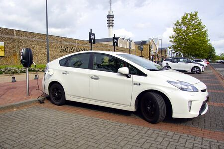 Lelystad, the Netherlands - September 1, 2019: White Toyota Prius being charged on a public parking lot. Nobody in the vehicle. Sajtókép
