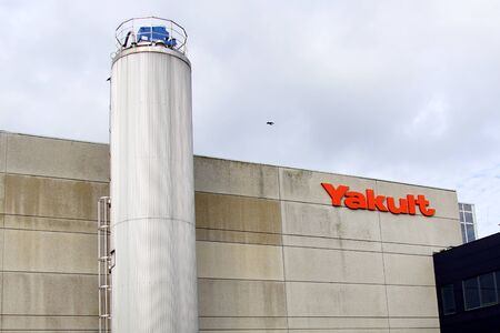 Almere, the Netherlands - October 5, 2019: Yakult wall logo and factory silo against a clouded sky. 에디토리얼