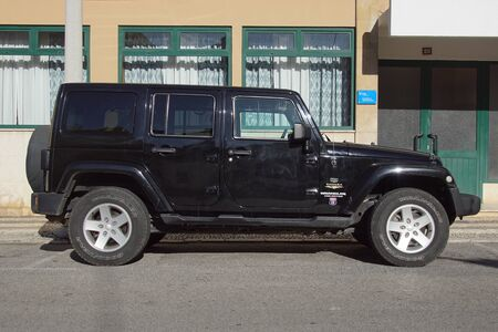 Faro, Portugal - December 28, 2019: Black Wrangler Sahara Unlimited parked by the side of the road. Nobody in the vehicle.
