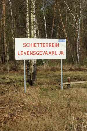 Harskamp, the Netherlands - February 18, 2020: Combined warning sign for danger to life and forbidden access at a Dutch army shooting area.