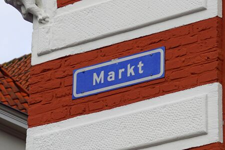 Hattem, the Netherlands - February 20, 2020: Blue street name sign Markt against a brick wall.
