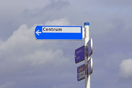 Hattem, the Netherlands - February 20, 2020: Dutch blue direction sign indicating the city center against a clouded sky.