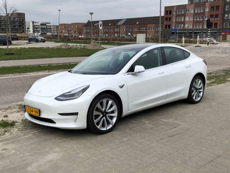 Almere, the Netherlands - March 18, 2020: White Tesla model 3 parked by the side of the road. Nobody in the vehicle.