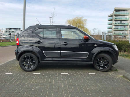 Almere, the Netherlands - March 17, 2020: Black Suzuki Ignis parked by the side of the road. Nobody in the vehicle. Editorial