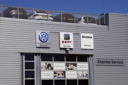 Naarden, the Netherlands - April 19, 2020: Wall logos and workshop entrance of Volkswagen, Seat and Skoda.