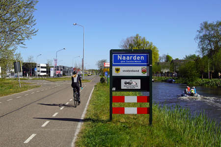 Naarden, the Netherlands - April 19, 2020: Unknown and unidentifiable recreationists passing the city entrance sign of Dutch town of Naarden, Gooise Meren.