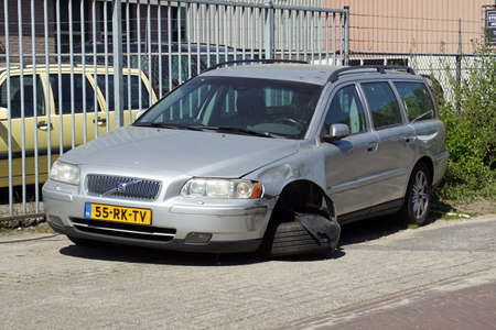 Naarden, the Netherlands - April 26, 2020: Side view of a wracked gray Volvo V70 by the side of the road. Nobody in the vehicle.