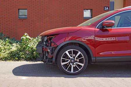 Naarden, the Netherlands - April 26, 2020: Wrecked red Nissan Qashqai by the side of the road. Nobody in the vehicle.