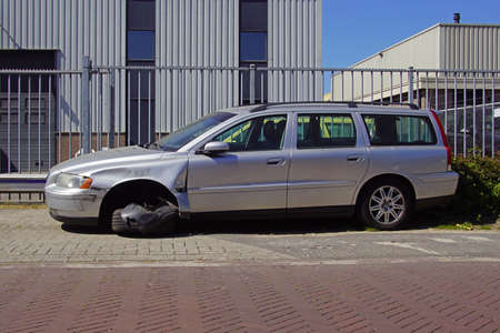 Naarden, the Netherlands - April 26, 2020: Wracked gray Volvo V70 by the side of the road. Nobody in the vehicle.
