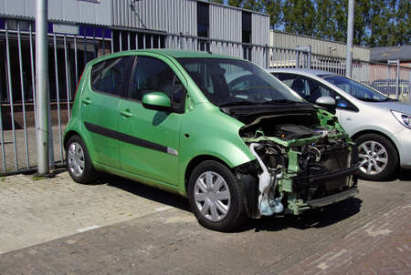 Naarden, the Netherlands - April 26, 2020: Wracked green Suzuki Splash. Nobody in the vehicle.