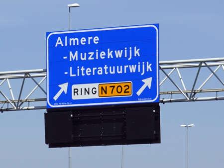 Almere, the Netherlands - May 8, 2020: Dutch highway exit sign for Almere Muziekwijk and Literatuurwijk.