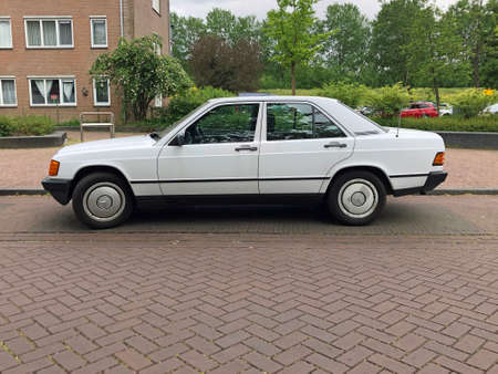Almere, the Netherlands - May 22, 2020: White Mercedes-Benz 190 E parked by the side of the road. Nobody in the vehicle.