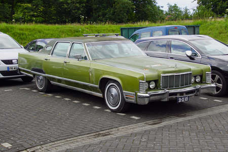 Pieterburen, the Netherland - July 16, 2020: Green Lincoln Continental Mark III parked on a public parking lot. Nobody in the vehicle.