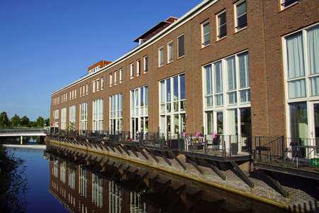Almere Poort, the Netherland - June 22, 2020: Dutch row houses on the waterside in the city of Almere.