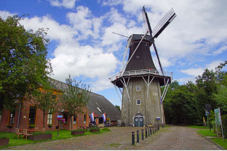 Eenrum, the Netherland - July 15, 2020: Historical Dutch flour mill 'De Lelie' and the entrance of the mustard museum in the town of Eenrum. 報道画像