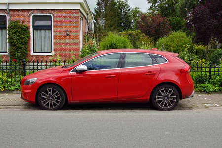 Pieterburen, the Netherland - July 16, 2020: Red Volvo V40 D2 parked on a public parking lot. Nobody in the vehicle. 報道画像