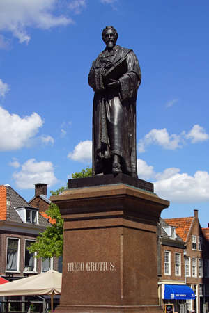 Delft, the Netherlands - August 5, 2020: Monument of Dutch lawyer and statesman Hugo Grotius against a partly clouded blue sky.