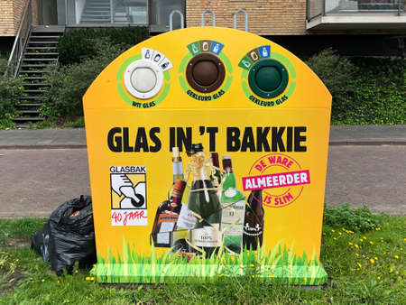 Almere, the Netherland - September 27, 2020: Yellow Dutch glass recycle container.