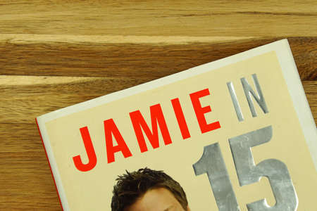 Zaandam, the Netherlands - November 21, 2020: Part of Jamie Oliver in 15 minutes book cover on a wooden kitchen table.