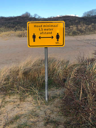 Veere, the Netherlands - January 2, 2021: Dutch attention sign warning hikers to keep minimal 1.5 meters away from other people. Editorial