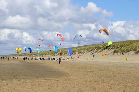 Noordwijk, the Netherland - May 2, 2021: Paraglider's soaring above Dutch dikes in the city of Noordwijk